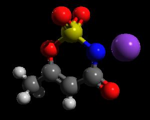 alt: Molekula Acesulfamu K. Zdroj Wikimedia Commons, autor NZLS11, licence Creative Commons CC0 1.0 Universal Public Domain Dedication. Černě atomy uhlíku, bíle vodíku, červeně kyslíku, modře dusíku, žlutě síry. Fialově je znázorněn kation draslíku.